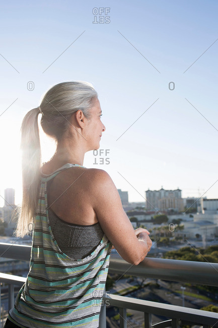 Mature woman in sports clothing leaning against city balcony