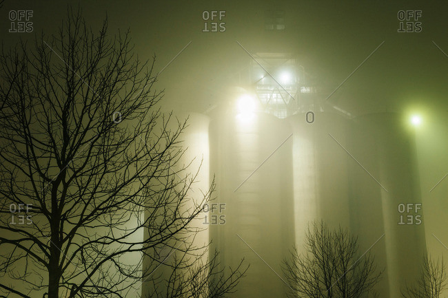 Misty view of industrial storage tanks and silhouetted trees at night, Seattle, Washington, USA