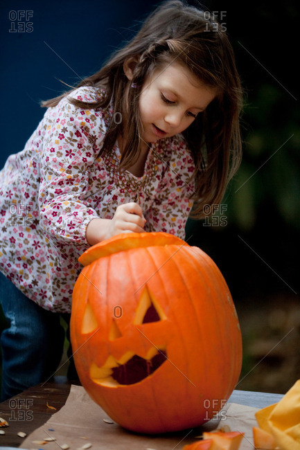 Young girl carving a pumpkin for Halloween