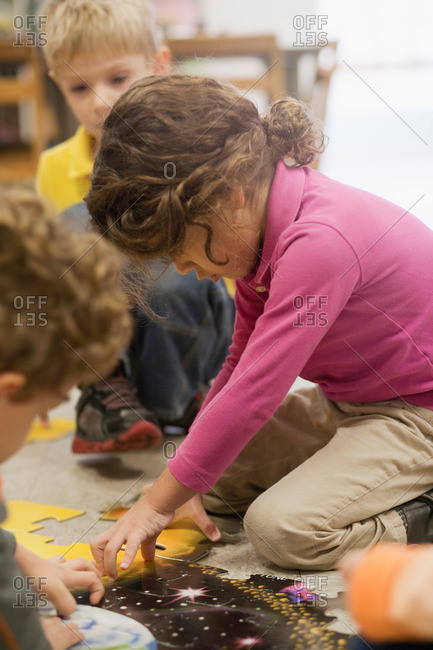 Toddlers playing jigsaw puzzle in classroom