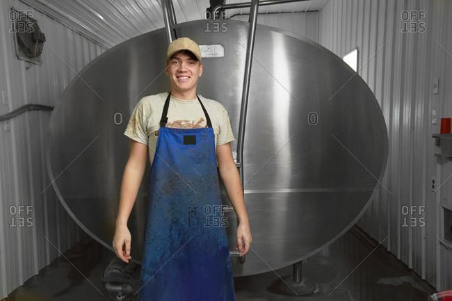 Portrait of teenage boy in front of milk tank in dairy farm milking shed