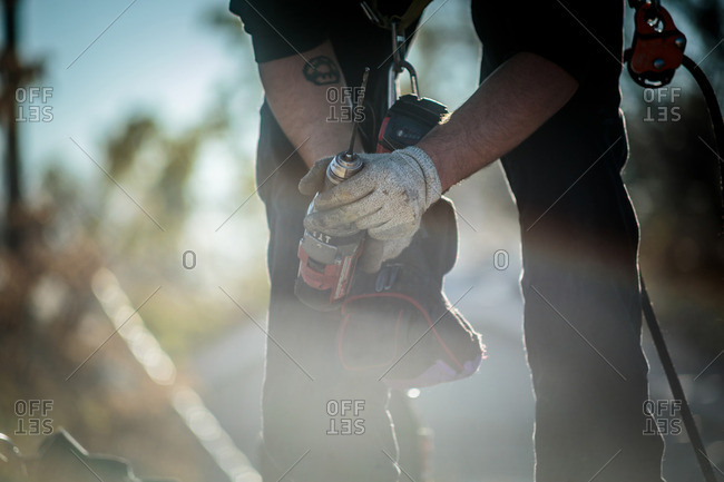 Solar panel installation worker with drill