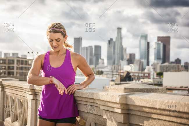 Young female runner checking wristwatch on bridge, Los Angeles, California, USA