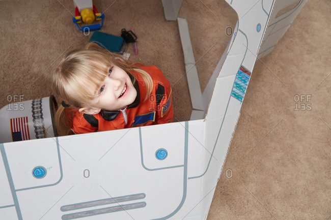 Young girl playing in cardboard spaceship wearing astronaut outfit