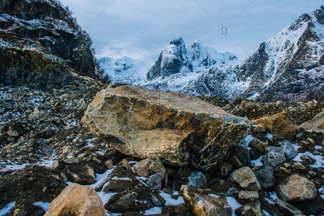 View of boulder, rocks and snow capped mountain, Reine, Lofoten, Norway