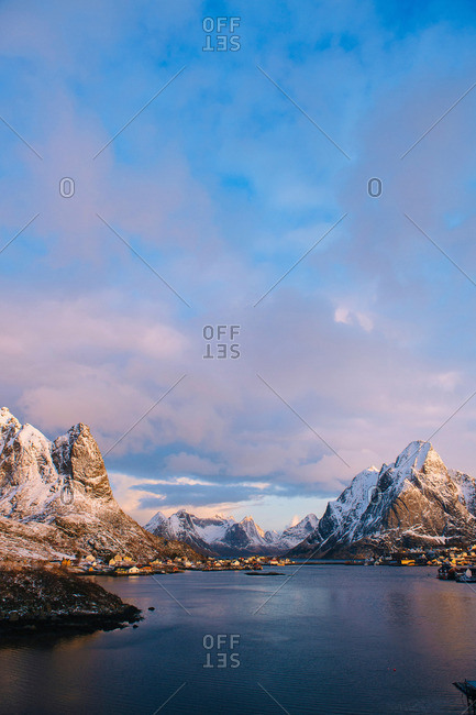 Distant view of waterfront village and snow capped mountains at dusk, Reine, Lofoten, Norway
