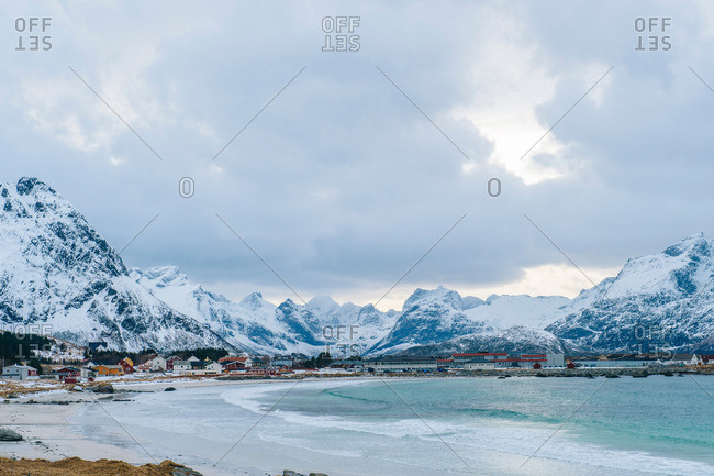 Distant view of waterfront village and snow capped mountains, Reine, Lofoten, Norway