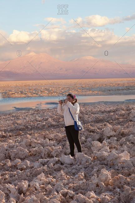 Young girl taking photograph of arid landscape of Salar de Atacama, San Pedro, Atacama, Chile