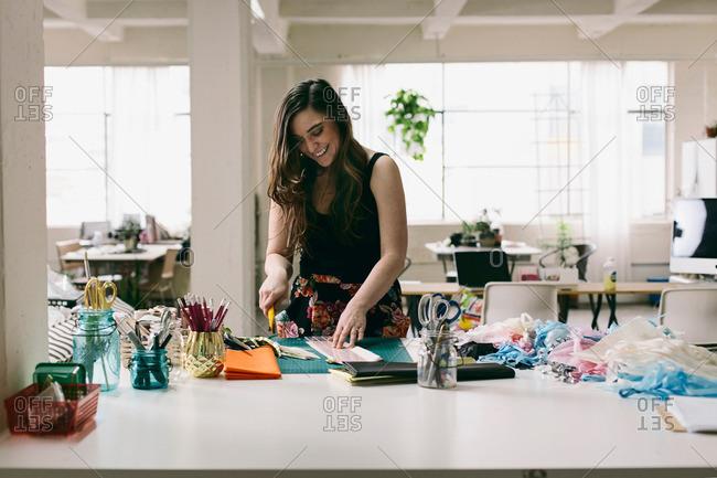 Female textile designer preparing textiles in design studio