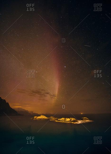 Aurora borealis disappearing over sea horizon, Reine, Norway