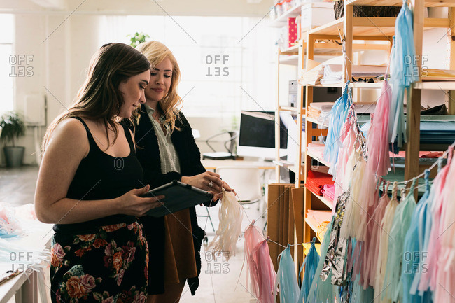 Two female designers using digital tablet in design studio