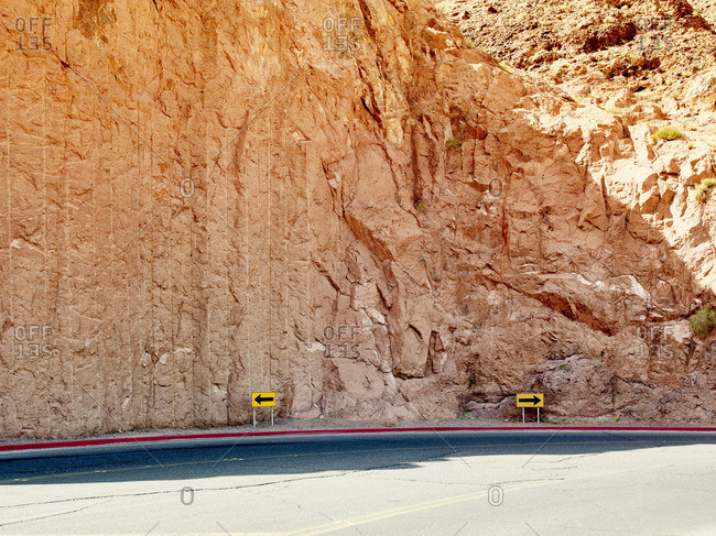 Road with yellow direction arrows in opposite direction,  Hoover Dam, Nevada, USA