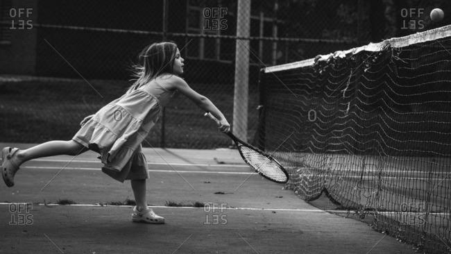 Little girl swinging a tennis racquet