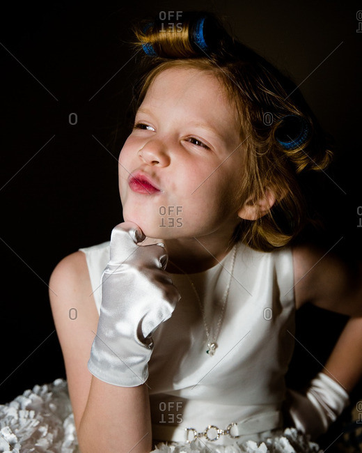 Girl with white gloves and rollers in her hair making funny face