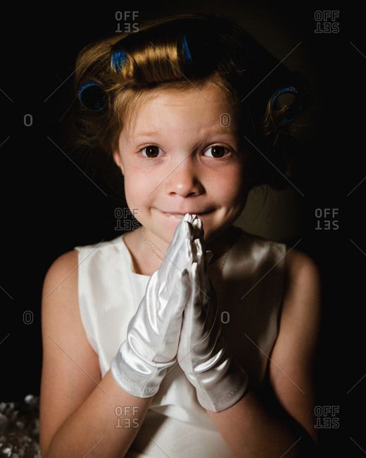 Little girl with white gloves and rollers in her hair