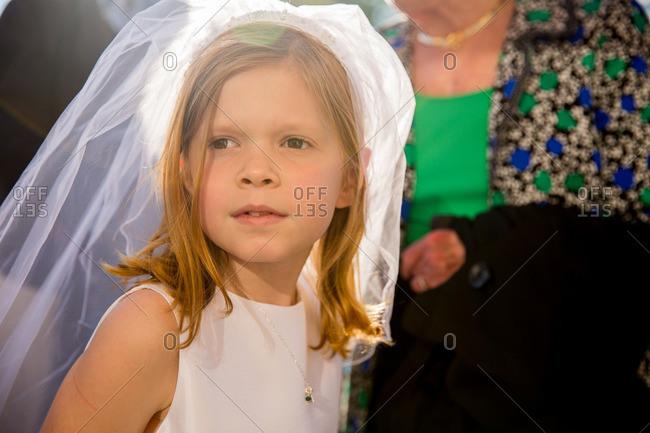 Little girl wearing white dress and veil