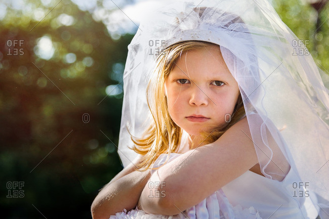 Little girl wearing white dress and veil pouting