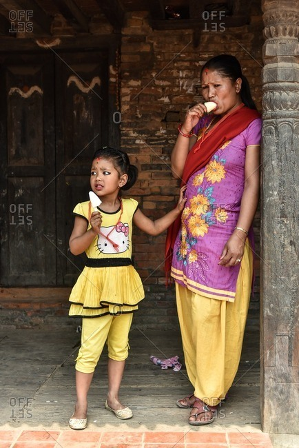 Bhaktapur, Nepal - April 12, 2016: Mother and daughter eating ice cream cones on a sidewalk in Bhaktapur, Nepal