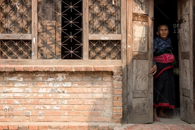 Bhaktapur, Nepal - April 13, 2016: Old woman standing in a doorway in Bhaktapur, Nepal