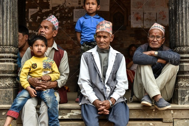 Bhaktapur, Nepal - April 12, 2016: Three generations of a family sitting between pillars in Bhaktapur, Nepal