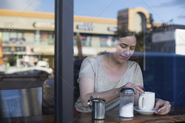 Woman stirring coffee in a caf�