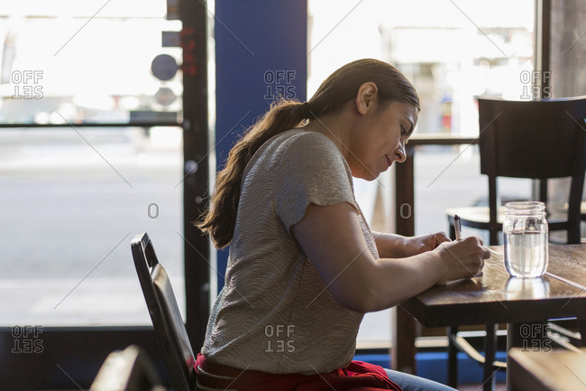 Waitress sitting at table writing a ticket
