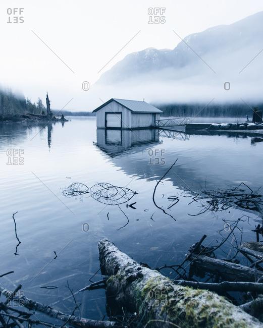 Boat house on a foggy lake