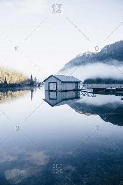 Boat house beneath foggy mountains