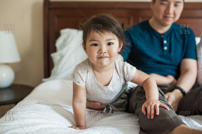 Little girl sitting with her dad on a bed