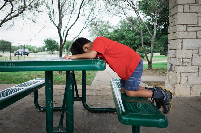 Young boy with his head down on a picnic table