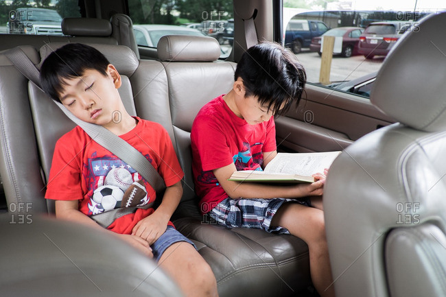Two brothers sitting in the back seat of their family's SUV