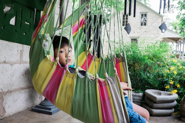 Portrait of a boy sitting in a hammock on his porch