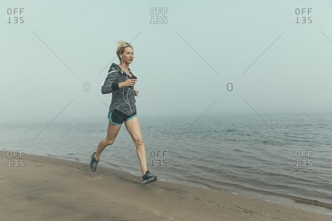 Woman jogging along a foggy beach