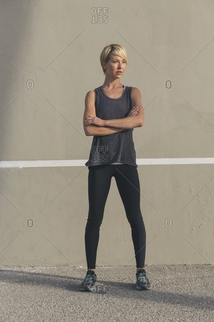 Portrait of a woman in workout clothing standing against a wall