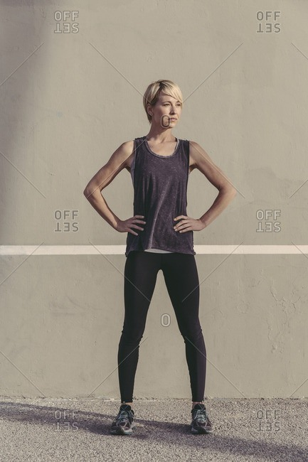 Portrait of a young woman in workout clothing standing against a wall