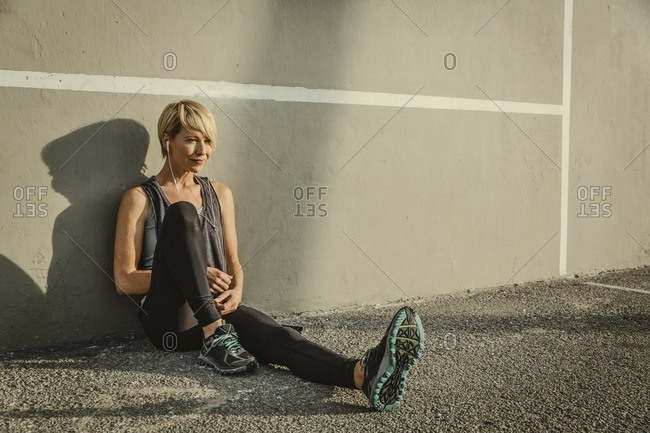 Portrait of a young woman in workout clothing sitting against a wall