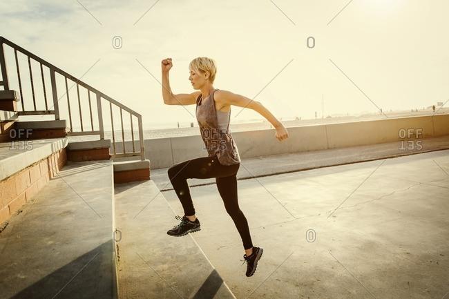 Woman doing a stair workout along a sunny beach