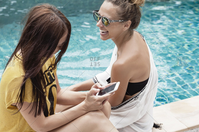 High angle view of happy woman using smart phone while relaxing with friend at poolside
