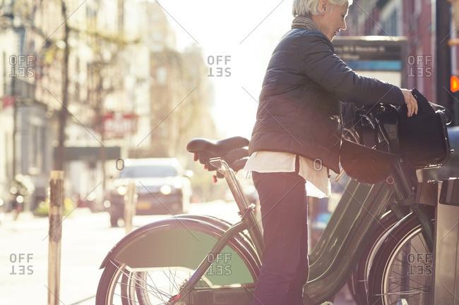 Side view of senior woman unlocking City Bike from rack