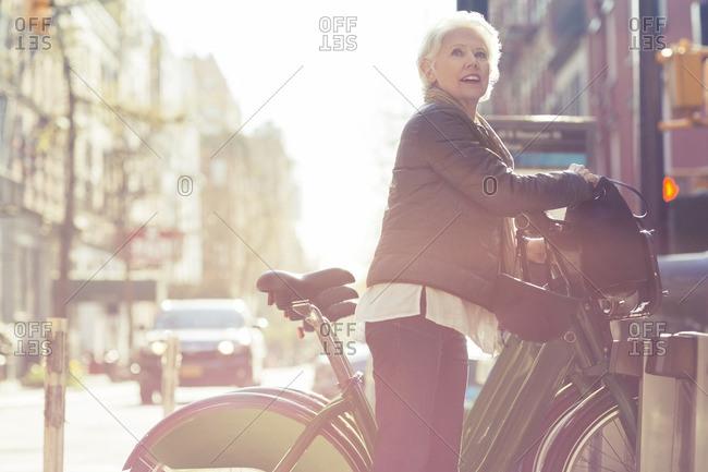 Senior woman looking away while unlocking City Bike from rack