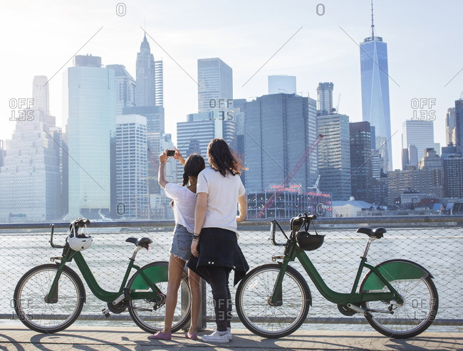 Rear view of couple photographing cityscape by river