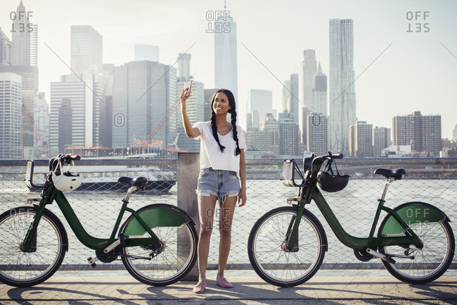 Happy woman taking selfie through mobile phone by bikes against cityscape