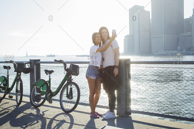 Happy couple taking selfie through mobile phone while standing by bikes during sunny day