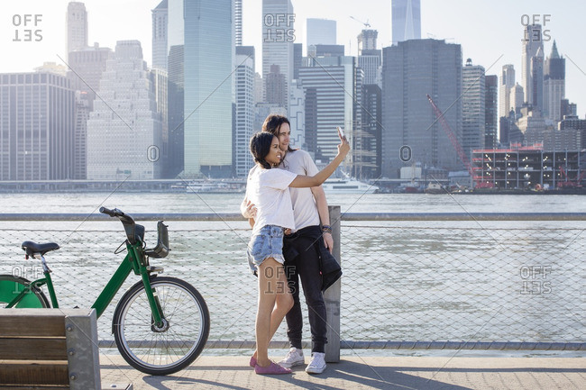 Couple taking selfie on mobile phone while standing by bike against cityscape
