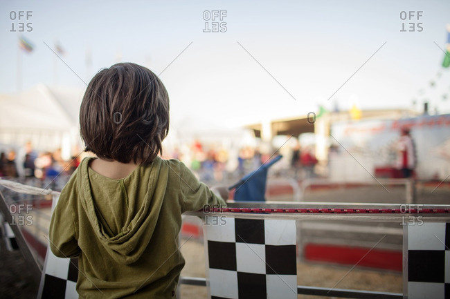 Rear view of boy standing by railing at amusement park