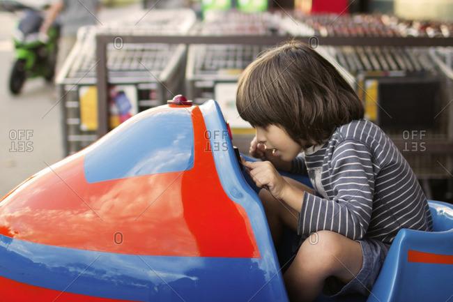 Boy sitting in toy car at amusement park
