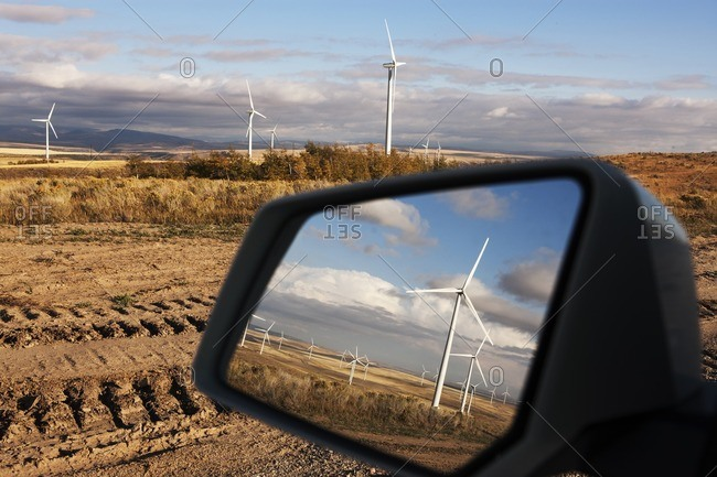 Windmills reflecting on side-view mirror of car at farm
