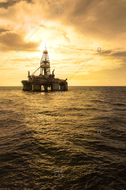 Oil platform in sea against cloudy sky