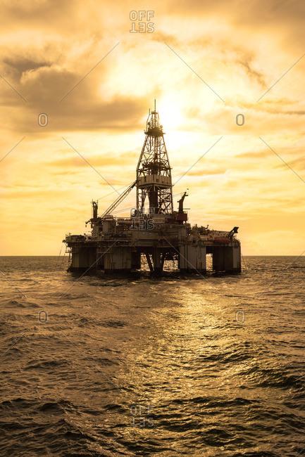 Oil rig in sea against cloudy sky
