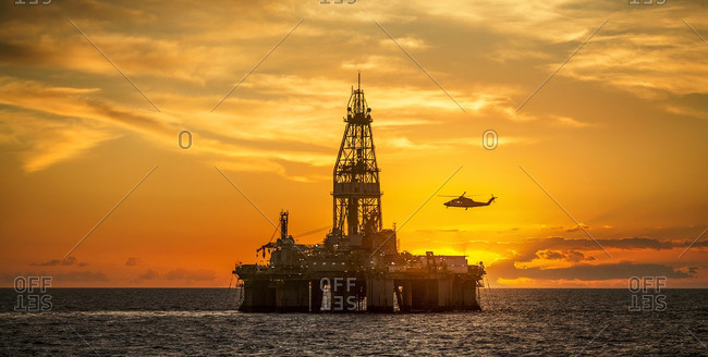 Helicopter flying over oil rig in sea against sky during sunset